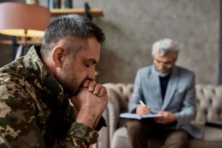 Get rid of all the pain. Middle aged military man closed eyes during therapy session with psychologist. Soldier suffering from depression, psychological trauma. PTSD concept