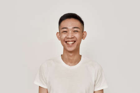 Happy guy. Portrait of young asian man with clean shaven face smiling at camera isolated over white background. Beauty, skincare, health concept