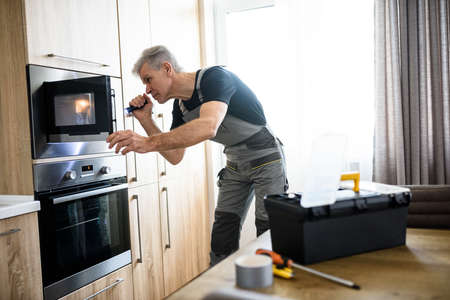 Here for Repairs. Aged repairman in uniform working, examining broken microwave in the kitchen using flashlight. Repair service concept