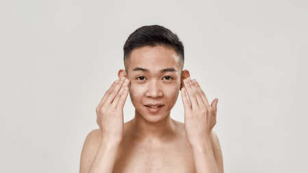Refresh. Portrait of shirtless young asian man rinsing his face after shaving looking at camera isolated over white background. Beauty, skincare routine concept