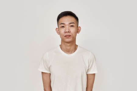 Clean skin. Portrait of young asian man with clean shaven face looking at camera isolated over white background. Beauty, skincare, health concept