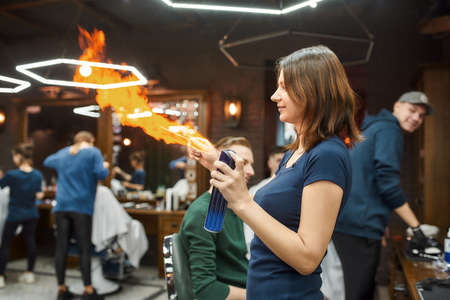 Hair fire treatment. Young professional barber girl heating tools for traditional shaving or hair removing under stream of fire at modern barber shop
