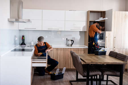 Let us work. Full length shot of two handymen, workers in uniform assembling kitchen cupboard, cabinet using screwdriver indoors. Furniture repair and assembly concept