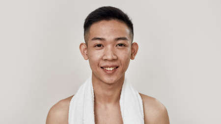Let the skin breathe. Portrait of shirtless young asian man with towel around his neck smiling at camera isolated over white background. Beauty, skincare routine concept