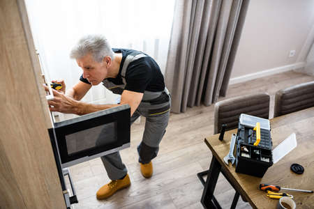 Full length shot of aged repairman in uniform working, fixing broken microwave in the kitchen using screwdriver. Repair service concept Imagens