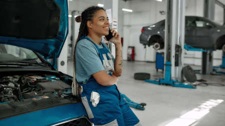 Young african american woman, professional female mechanic talking on phone, leaning on a car with open hood at auto repair shop Stock fotó
