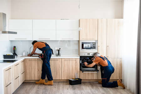 Pay and have it your way. Two handymen, workers in uniform fixing, installing furniture and equipment in the kitchen, using screwdriver indoors. Furniture repair and assembly concept