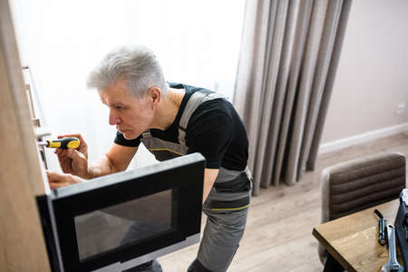 Aged repairman in uniform working, fixing broken microwave in the kitchen using screwdriver. Repair service concept