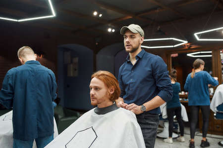 Young professional barber serving client, young redhead guy sitting in barbershop chair