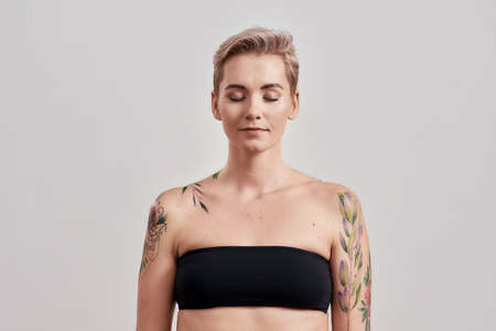 Portrait of a young attractive half tattooed woman with perfect skin and makeup posing with closed eyes isolated over light background