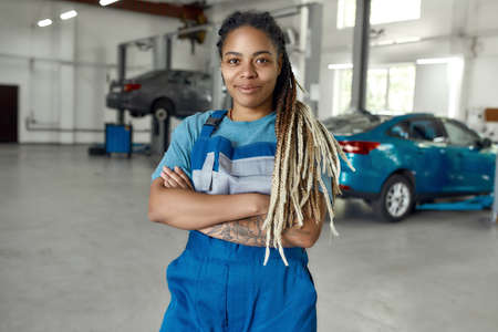 Get instant help to your car. Portrait of young african american woman, professional female mechanic in uniform smiling at camera, standing in auto repair shop. Car service, repair and people concept Stock fotó