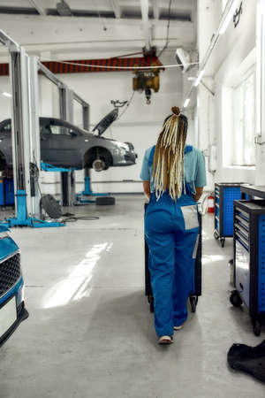 African american woman, professional female mechanic in uniform pulling, carrying tool box cart in auto repair shop. Car service, maintenance and people concept