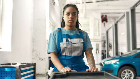 Doctor for your car. African american woman, professional female mechanic pulling, carrying tool box cart in auto repair shop. Car service, maintenance and people concept Stock fotó
