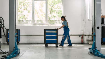 African american woman, professional female mechanic pulling, carrying tool box cart in auto repair shop. Car service, maintenance and people concept Stock fotó
