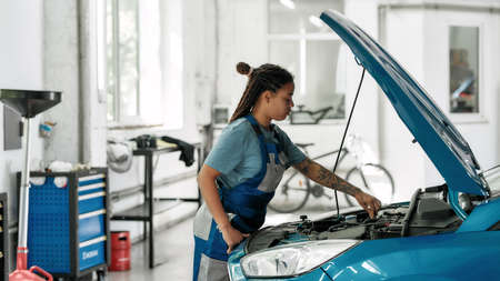 Quality in Every Work. Young african american woman, professional female mechanic looking, examining under hood of car at auto repair shop Stock fotó