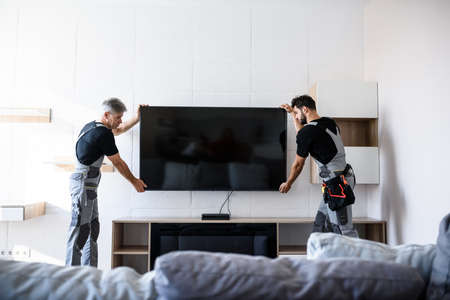 Two professional technicians, workers in uniform installing television on the wall indoors. Construction, maintenance and delivery concept