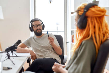 Male blogger, man in headphones listening to woman while talking, recording conversation, interview with her for video blog 免版税图像
