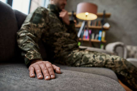 Close up of hand of military man in camouflage sitting on the couch during therapy session. Soldier suffering from depression, psychological trauma. PTSD concept Banque d'images