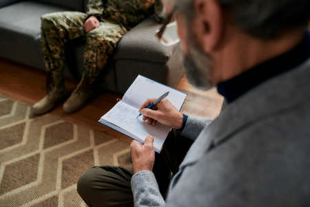 Notebook. Close up of hands of psychologist making notes while communicating with military man during therapy session. Soldier suffering from depression, psychological trauma. PTSD concept
