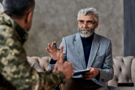 Fixing you. Portrait of mature psychologist communicating with military man and making notes during therapy session. Soldier suffering from depression, psychological trauma. PTSD concept