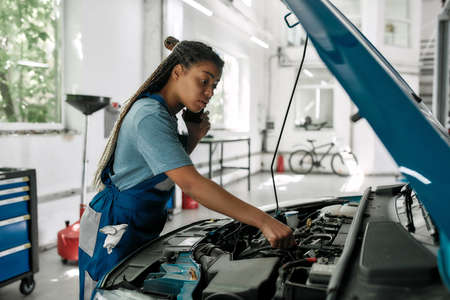 Honest services. Young african american woman, professional female mechanic talking on phone, while examining engine under hood of car at auto repair shop Banque d'images