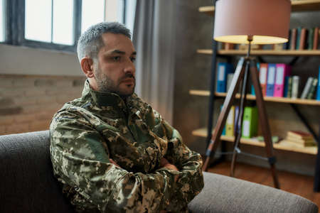 Remembering. Sad middle aged military man looking thoughtful, sitting on the couch during therapy session. Soldier suffering from depression, psychological trauma. PTSD concept