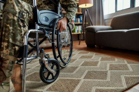 Disability. Cropped shot of disabled military man wearing camouflage in a wheelchair during therapy session in the living room. PTSD concept
