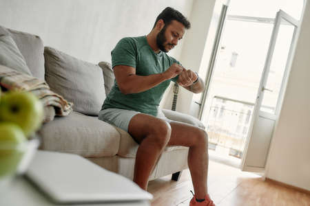 Morning routine. Young active man checking time in smartwatch during break, doing morning workout at home. Fitness, motivation concept Banque d'images