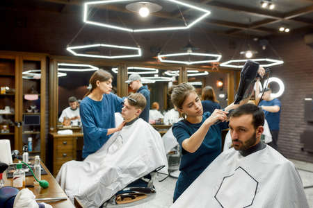 Working in barbershop. Professional young barber girl drying hair of young handsome bearded man visiting modern barbershop