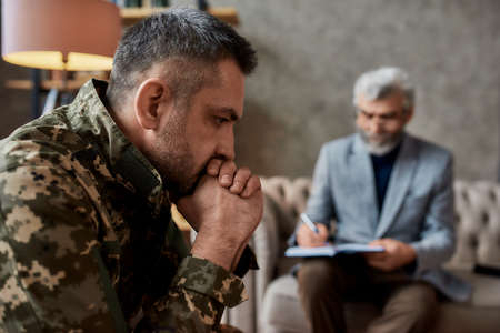 Need help. Middle aged military man looking thoughtful during therapy session with psychologist. Soldier suffering from depression, psychological trauma. PTSD concept Banque d'images