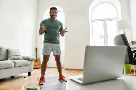 Stay in touch. Full length shot of male fitness instructor greeting viewers while streaming, broadcasting video lesson on training at home using laptop. Sport, online gym concept