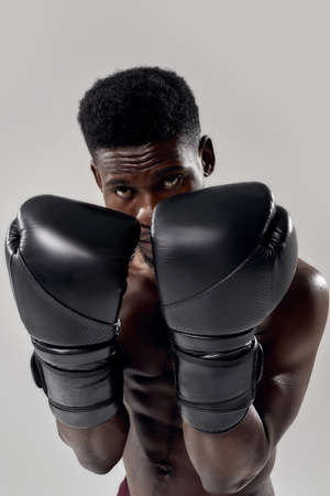 Portrait of young muscular african american male boxer looking at camera, wearing boxing gloves, standing in defence position isolated over grey background Stock Photo