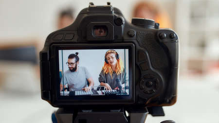 Woman with dreadlocks singing and playing. Female and male blogger recording making music using synthesizer, drum pad machine. Focus on camera screen