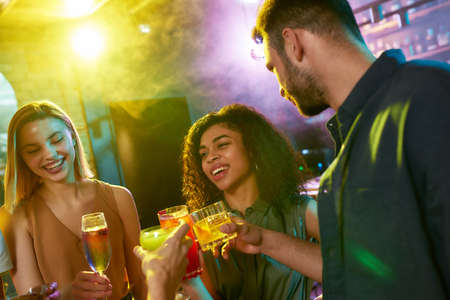 A group of friends, young women and man chatting while having fun, drinking cocktails, spending time together in the night club