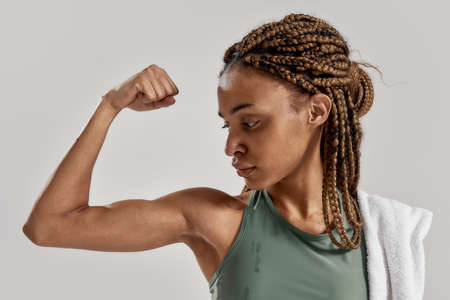 Get stronger. Close up portrait of young sportive mixed race woman showing her biceps after intensive training isolated over grey background