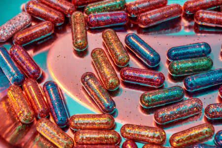 Creative concept with many colorful glitter pills scattered, lying randomly in metal box. Minimal style, art concept Zdjęcie Seryjne