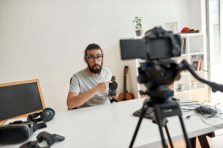 Male technology blogger making faces, holding, pointing at headphones, recording video blog or vlog about new gadgets at home studio