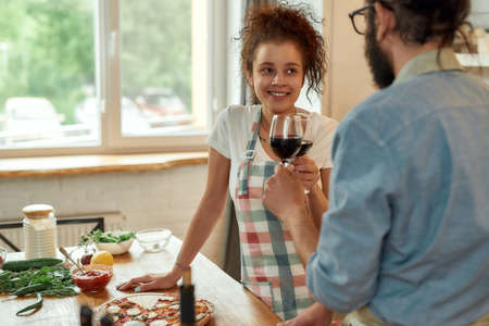 Happy girlfriend. Young man and woman in apron looking at each other, having toast, drinking wine while standing in the kitchen. Love, relationships concept