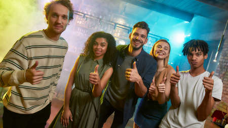 Young men and women smiling, showing thumbs up while posing together for camera. Multiracial group of friends hanging out at party in the bar Stockfoto