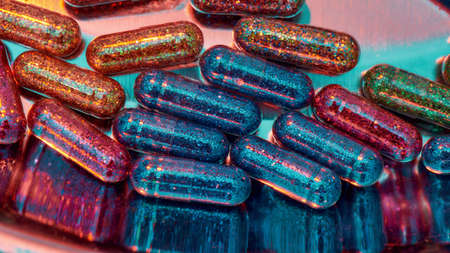Creative concept with many colorful glitter pills scattered, lying randomly in metal box. Minimal style, art concept