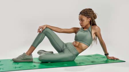 Young sportive mixed race woman in sportswear looking aside, doing exercises, sitting on a mat isolated over grey background. Healthy lifestyle and sports concept