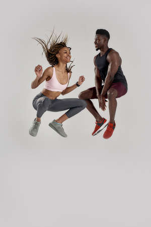 Full length shot of young muscular african american man and sportive mixed race woman jumping, celebrating great accomplishment, rejoicing isolated over grey background