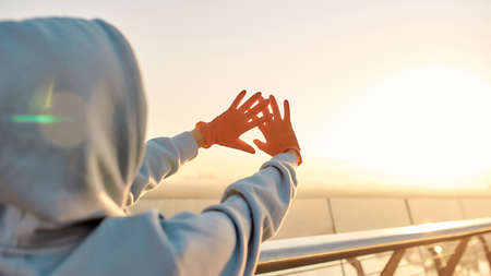 Protection against infection. Woman wearing protective gloves, reaching out her hands to the light while watching the sunrise. Coronavirus, epidemic, safety concept