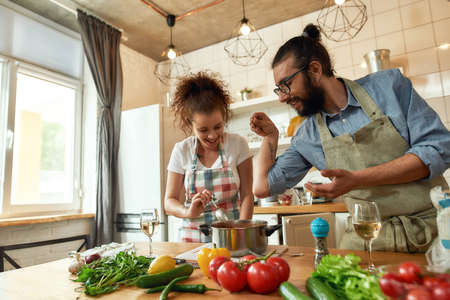 Italian man adding pepper, spice to the soup while woman stirring it and smiling, couple preparing a meal together in the kitchen