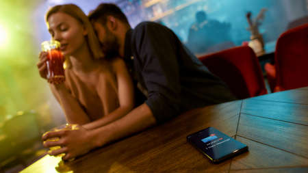 Message from wife. Unfaithful man spending time with another woman flirting in the bar, enjoying drinks and conversation. Cheating, infidelity concept Banque d'images