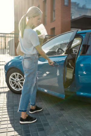 Full length shot of young woman opening the blue car door while holding grocery bag after shopping in the supermarket