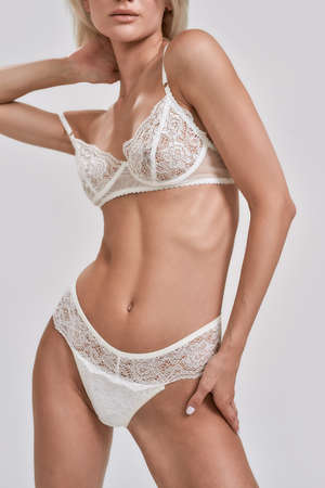 Cropped shot of sensual young woman with fit slim body wearing sexy white lace lingerie posing isolated over grey background