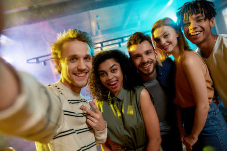Close up shot of young men and women smiling while taking selfie. Multiracial group of friends hanging out at party in the bar