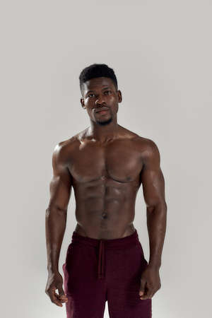 Strength. Muscular african american man looking at camera, showing his torso while posing shirtless isolated over grey background. Sports, workout, bodybuilding concept