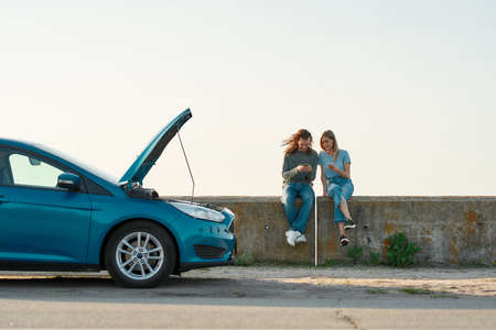Outdoor shot of couple of travelers having problems with the car, man and woman sitting near broken car with open hood and looking for a phone number of assistance, trying to solve problem